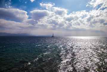 日が射す海に浮かぶヨット