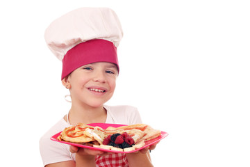 happy little girl cook with sweet crepes