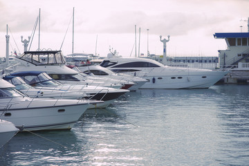 Yachts on the pier in the port in cloudy weather