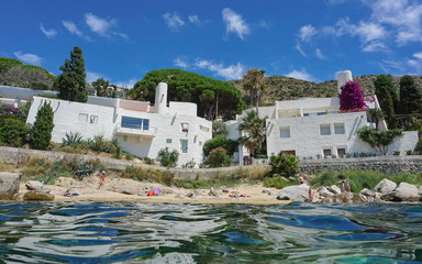 Waterfront houses on the Mediterranean sea shore with sand and rocks, Spain on the Costa Brava, Catalonia, Canyelles Petites, Roses, Girona, seen from water surface