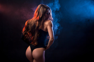 Young dark-haired woman in black lingerie posing against a background of  blue smoke from a vape on a black isolated background