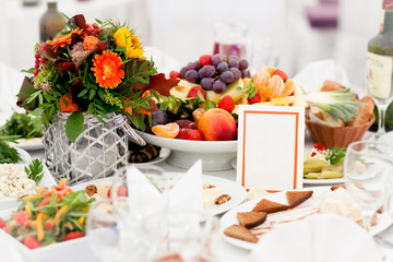 A beautifully decorated festive table with a meal in the center of which stands a vase with a bouquet of flowers, a plate of fruit, and a postcard on which you can write something