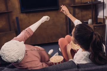 rear view of woman eating popcorn while watching film together with manikin at home, perfect relationship dream concept