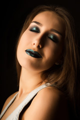 Tender brunette lady with art metallic green makeup posing with closed eyes. Closeup portrait at studio on a dark background