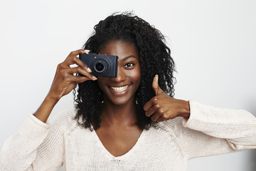 Smiling beautiful woman with thumbs up and camera
