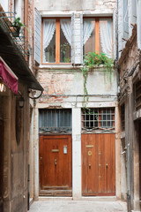 Walk through the charming, narrow streets of Venice, typical but magical view - alley between tenement houses