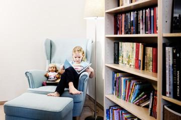 blondes mädchen beim lesen mit puppe