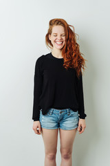 Fun happy young redhead woman standing grinning