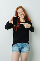 Smiling attractive woman pointing to her mobile