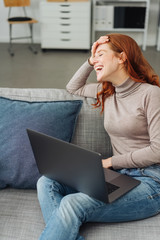Woman laughing while sitting on sofa with laptop