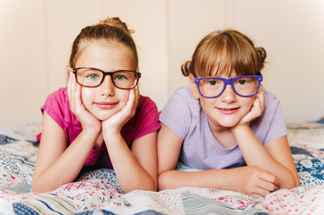 Portrait of 2 funny girls resting on the bed, wearing eyeglasses
