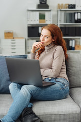Young woman sitting with laptop on sofa at home