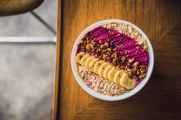 Superfood tropical smoothie bowl with dragon fruits, banana, granola on a wooden coffee table. Minimal food photography concept. Flatlay, copyspace