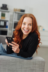 Young smiling woman with mobile phone on sofa