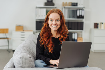 Young smiling woman sitting with laptop on sofa