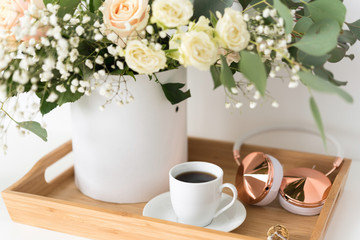 Blush wedding bouquet with roses, baby's breath and eucaluptus in wooden tray with coffee and hedphones