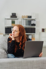Young thoughful woman sitting with laptop on sofa