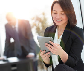 business woman with digital tablet on background of office.