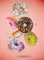 Tasty doughnuts in motion falling on pastel red background.