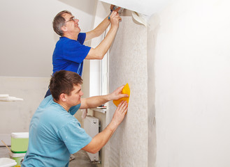 two workers smoothing wallpaper