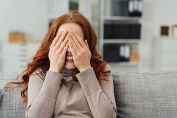 Young redhead woman covering her eyes