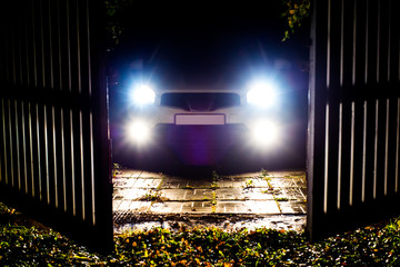 The car stands on the territory of the house at night. Light headlights through the fence