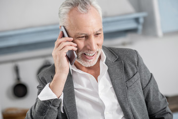 Being in all ears. Handsome mature man keeping smile on his face and holding his gadget near ear while having pleasant talk