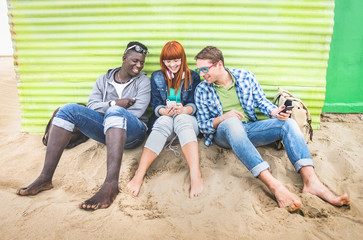 Group of happy multiracial friends having fun together using mobile smart phone - Young hipster people addicted by smartphone on social network community - Neutral cloudy filtered color tone