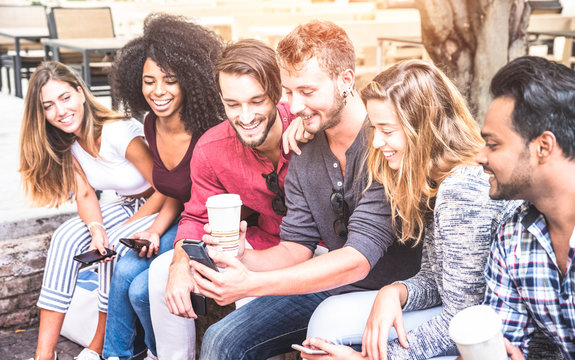Multiracial friends group using smartphone at university college - Young people addicted by mobile smart phone - Technology concept with connected trendy millennials - Soft pink pastel sunshine filter