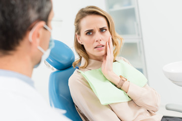 Female patient concerned about toothache in modern dental clinic