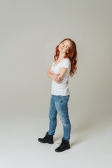 Trendy young redhead woman in jeans and boots