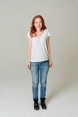 Delighted young redhead woman in jeans