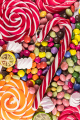Background of colorful chocolate candies, lollipops, candy cane and marshmallows