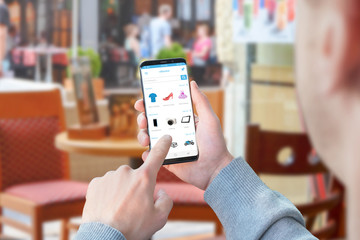 Guy use online store app for shopping clothes, electronic, motors. Coffee shop in background.
