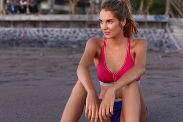 Outdoor shot of thoughtful female jogger in active clothing, sits on sand after long run distance, has determined facial expression. Cute young woman with athletic legs has break during workout
