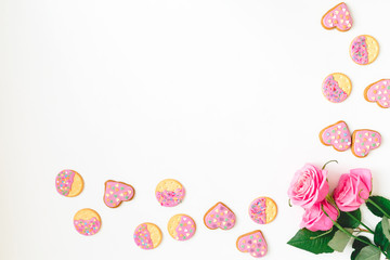 Gingerbread cookie with pink glaze and roses flower on white background. Flat lay. Top view. Woman day background