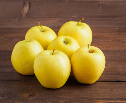 Golden Delicious. Juicy ripe fresh yellow apples on a brown wooden background, side view.