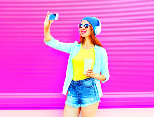 Fashion smiling woman takes a picture self portrait on smartphone in shorts, wireless headphones on pink background