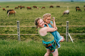 Tilt shift blurred expressive mood potrtrait of two little sisters resting outdoor in summer together. Young girls with emotional faces. Chilhood in village. Funny kids near grazing horses field.