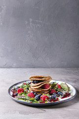 Vegan chickpea pancakes served in plate with green salad young beetroot leaves, sprouts, berries, berry sauce over grey kitchen table. Copy space. Healthy eating