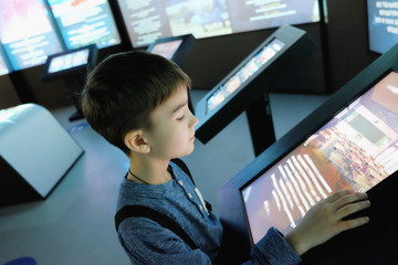 child examines the touchscreen in the interactive Museum Fototapete