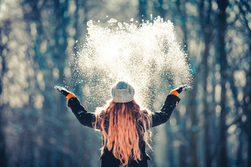 Young girl throwing snow in the air at sunny winter day, back view