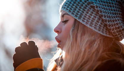 Woman breathing on her hands to keep them warm in cold winter day