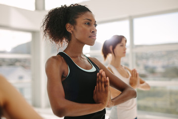 Women practice yoga together in gym