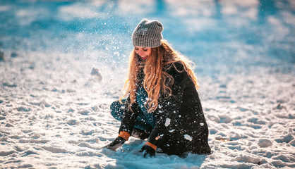Smiling woman throwing snow in the air at sunny winter day