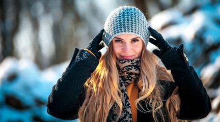 Young woman in the winter park at sunny day, warm clothes