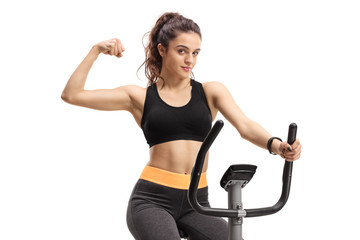 Teenage girl exercising on a cross-trainer machine and flexing her biceps