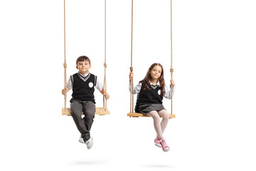 Schoolboy and a schoolgirl sitting on wooden swings