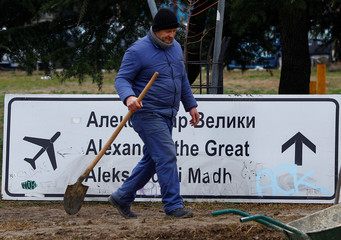 A worker passes a sign for Alexander the Great Airport which was removed due to road construction in Skopje