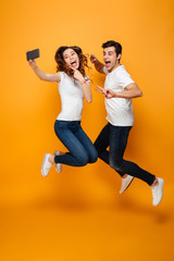 Image of two joyful man and woman 20s making selfie on cell phone while jumping and gesturing together over yellow background